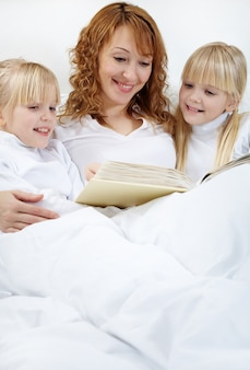 Mother reading her daughters in bed