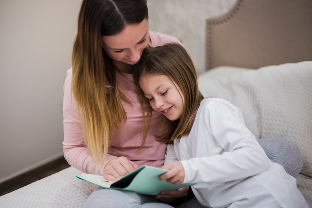 Mother reading together with daughter
