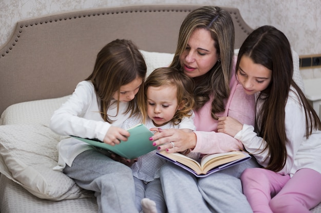 Mother reading together with daughters