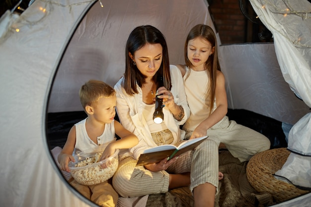 Mother reads a book of fairy tales for her children while sitting in a tent at night. mom son and daughter reading a book with a flashlight in their hands