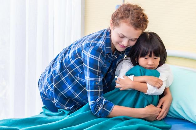 Мать успокаивает и обсуждает ее дочь. пациент девушка грустно на спальне больницы.