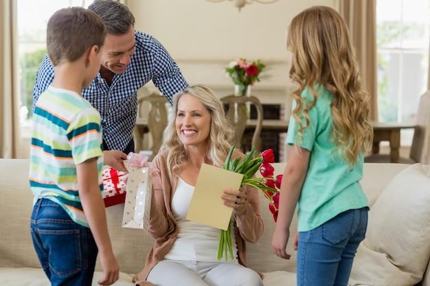 Мать получает подарок от своих детей и мужа в гостиной