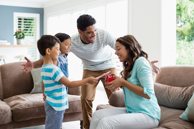 Mother receiving a gift from his kids and husband in living room