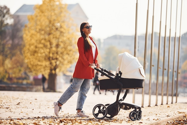 Mother in red coat have a walk with her kid in the pram in the park at autumn time.