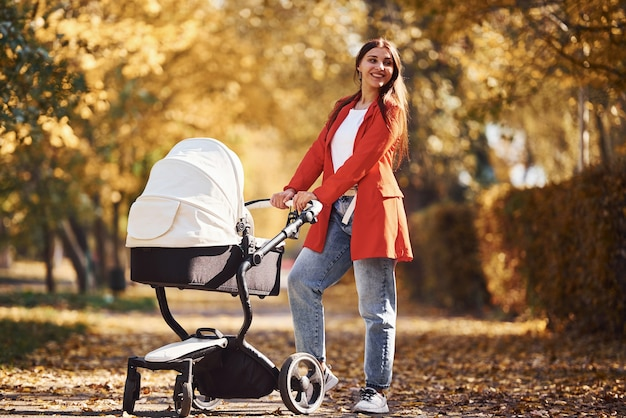 Mother in red coat have a walk with her kid in the pram in the park with beautiful trees at autumn time.
