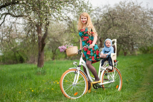 Mother riding bicycle with baby in bicycle chair