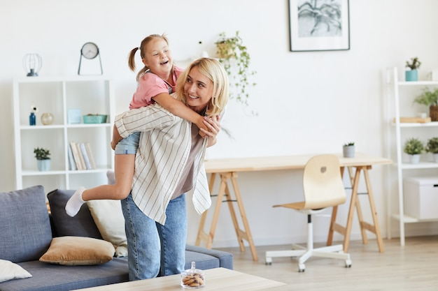彼らが居間で遊んでいる間、彼女の背中にダウン症で彼女の娘に乗っている母