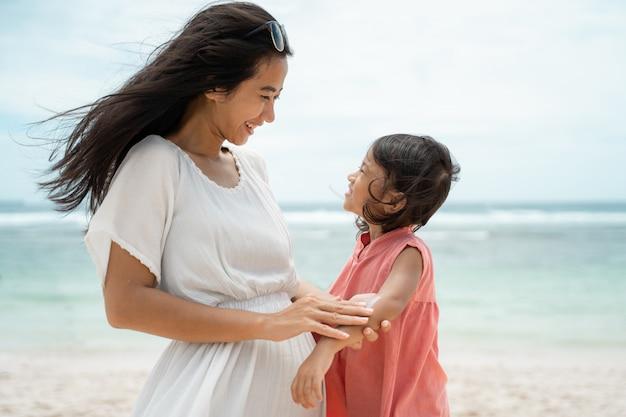 Мать втирает солнцезащитный крем в кожу дочери