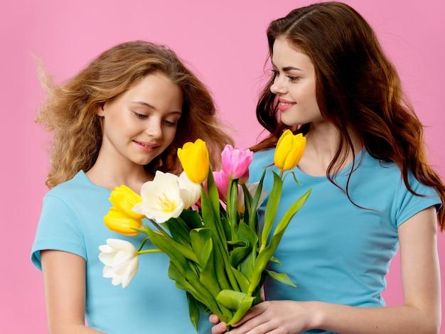 어머니의 날, 꽃과 함께 스튜디오에서 포즈를 취하는 아이를 가진 젊은 여성, 여성의 날과 어머니의 날 선물