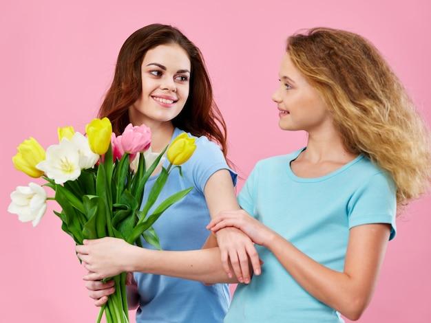 День матери, молодая женщина с ребенком позирует в студии с цветами, подарок на женский день и день матери
