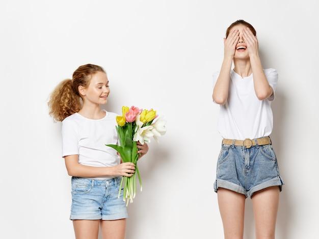母の日、花を持つポーズをとる子供を持つ若い女性、女性の日と母の日への贈り物