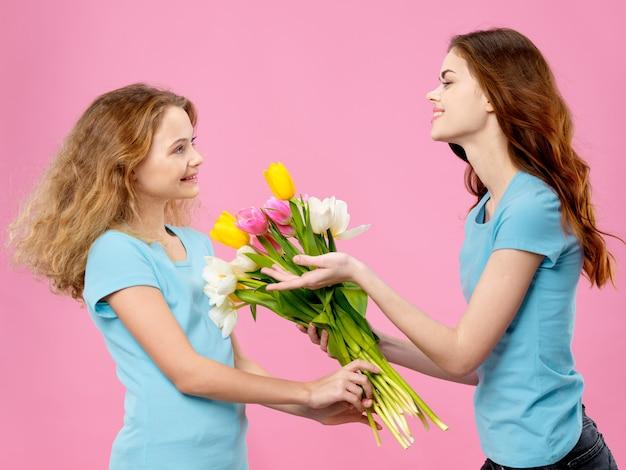 어머니의 날, 꽃과 함께 포즈를 취하는 아이를 가진 젊은 여성, 여성의 날과 어머니의 날 선물