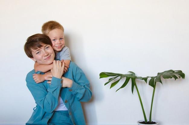 어머니의 날과 사랑. 파란색 천 포옹에 아들과 함께 행복 한 엄마. 흰 벽에 격리. 복사 공간. 냄비에 야자수. 아이와 게임