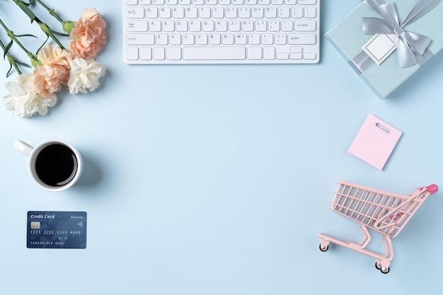 オフィスの青いテーブル デスクの背景にカーネーションの花を使った母の日購入ギフト デザイン コンセプト