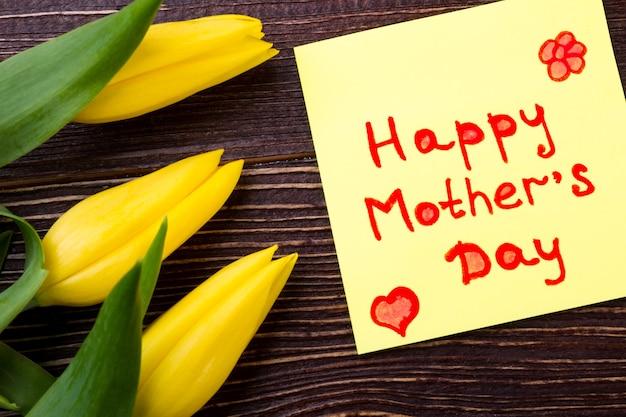 어머니의 날 카드와 튤립입니다. 인사말 종이와 꽃입니다. 엄마를 위한 밝은 선물을 만드세요. 휴가의 기대.