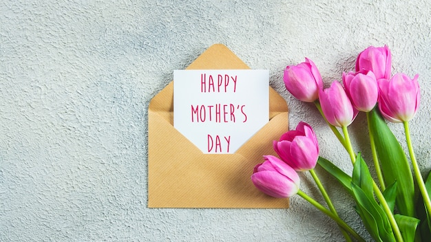 Mother's day card. pink tulips flowers and card with text on concrete background. flat lay, top view. banner