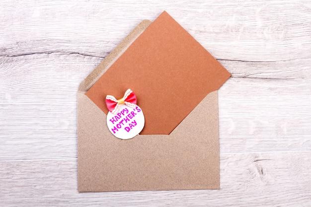 弓で母の日カード。木製の表面の封筒。手作りであなたの創造性を表現してください。お母さんのためにすべての最高を願っています。