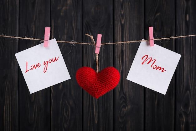 Открытка ко дню матери с красным сердцем и бумажными наклейками на веревке