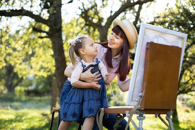 День матери, детское искусство и концепция творчества. открытый портрет красивой молодой мамы и милой трехлетней маленькой дочери, рисующей на мольберте картину в красивом зеленом парке или саду весной.