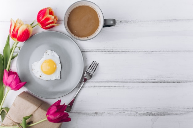 Mother's day composition. breakfast with tulips on white background.