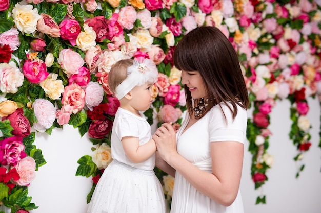 Концепция дня матери - счастливая красивая мать с маленькой дочерью на фоне стены цветов