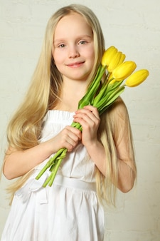 母の日-花のチューリップを持つかわいい子供
