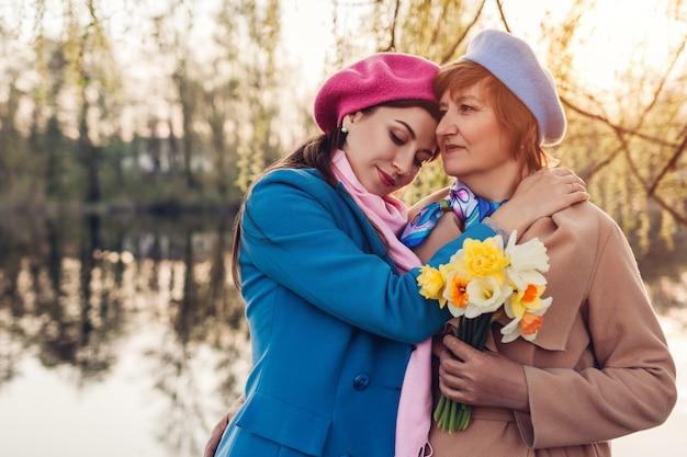 День матери. дочь, дающая ее старшей матери букет цветов. семья гуляя в парк весны рекой обнимая.