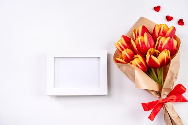 母の日のデザインコンセプト、チューリップの花の束、-明るい白の背景のテーブル、上面図、フラットレイ、コピースペースに分離された美しい赤、黄色の花束