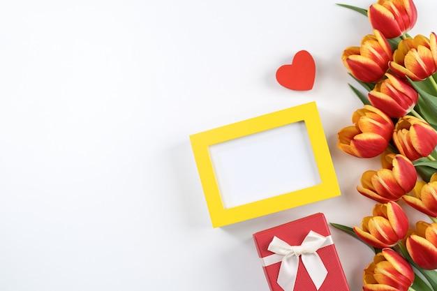 母の日のデザインコンセプト、チューリップの花の束-白い背景のテーブル、上面図、フラットレイ、コピースペースで隔離の美しい赤、黄色の花束