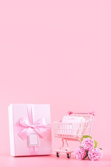 母の日のホリデーギフトのデザインコンセプト、ラップされたボックス、ショッピングカート、バッグ、淡いピンクの背景に分離されたピンクのカーネーションの花の花束、コピースペース。