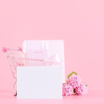 어머니의 날 휴일 선물 디자인 개념, 분홍색 배경, 복사 공간에 고립 된 포장 된 선물 상자 핑크 카네이션 꽃 꽃다발.