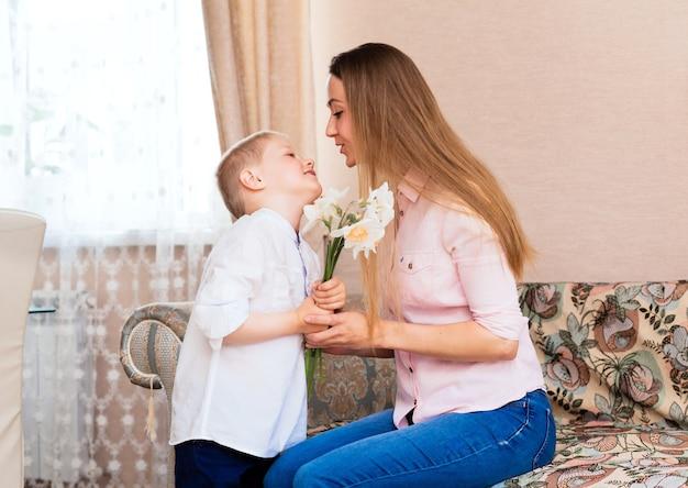 母の日、休日、家族のコンセプト-幸せな幼い息子は、自宅で笑顔の母親に花を贈ります。子供がお母さんに水仙の花束を贈る