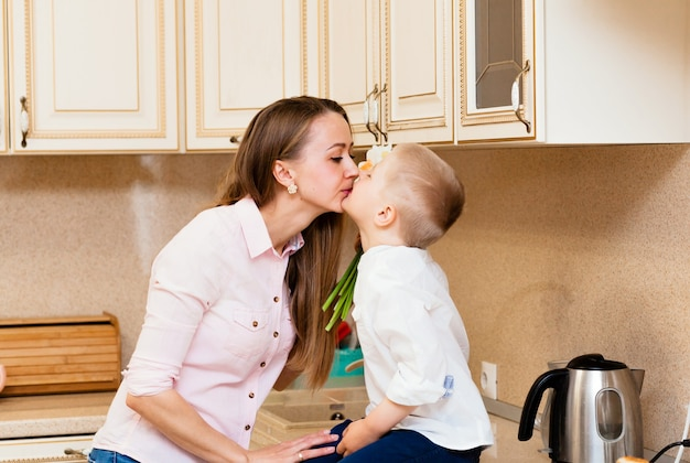 Mother's day, holidays and family concept - happy little son gives flowers to his smiling mother at home. a child gives mom a bouquet of daffodils
