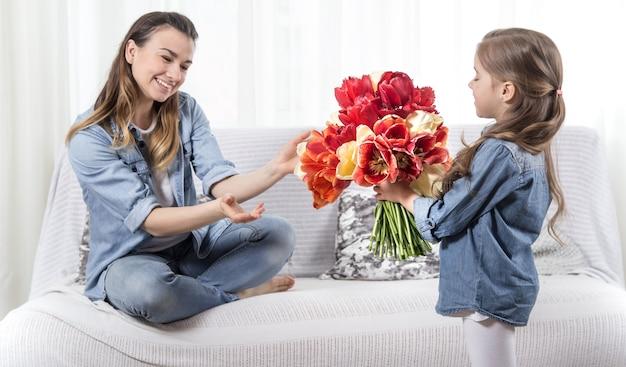 母の日。花を持つ小さな娘は彼女の母親を祝福します
