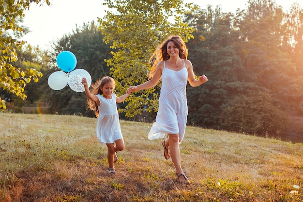 Mother's day. little girl running with mother and holding baloons. family having fun