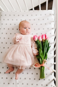 Mother's day message with the newborn baby girl who holding the flower and lying on a bed with a bouquet of pink tulips.