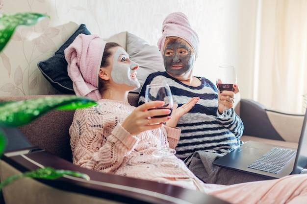 母の日。母と彼女の大人の娘は自宅で顔のマスクを適用しました。ワインを飲みながら話している女性