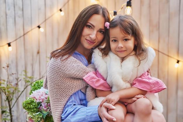 Открытка ко дню матери. мама женщины и девочка обнимаются в саду. пикник на заднем дворе. день защиты детей. счастливая семья на природе
