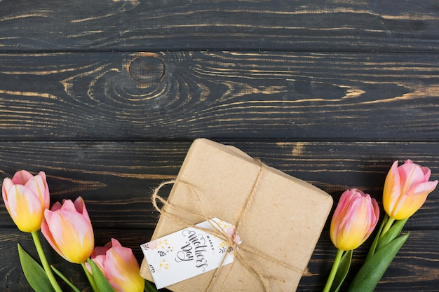 Mother`s day tag on gift box around tulips