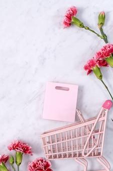 母の日、バレンタインデーの背景デザインのコンセプト、大理石のテーブル、平面図、フラットレイ、コピースペースに美しいピンク、赤のカーネーションの花の花束。