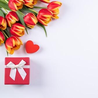 母の日、バレンタインデーの背景、チューリップの花の束-白いテーブルに分離された美しい赤、黄色の花束、上面図、フラットレイ、モックアップデザインコンセプト。
