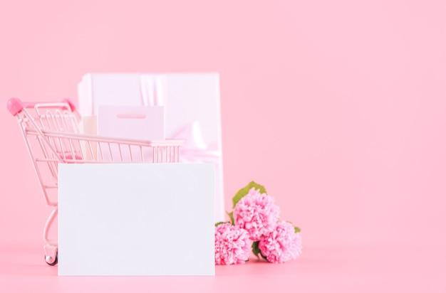 母の日、バレンタインデーのホリデーギフトのデザインコンセプト、淡いピンクの背景に分離されたラップボックス付きのピンクのカーネーションの花の花束、コピースペース。