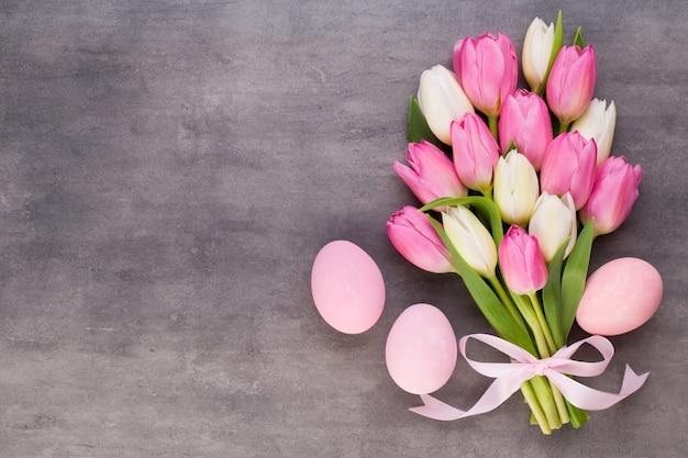 母の日、女性の日、イースター、ピンクのチューリップ、灰色の背景にプレゼント。