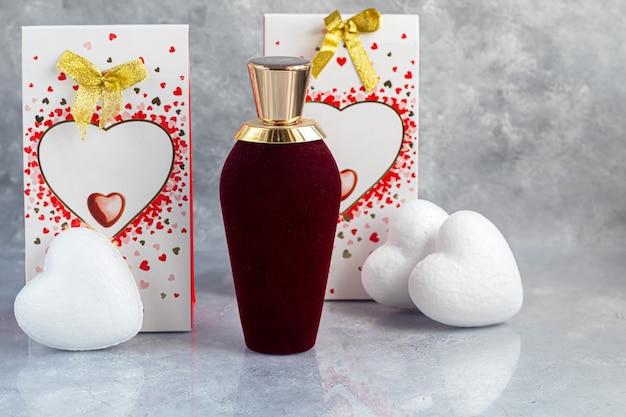 母の日、女性の日、バレンタインデーまたは誕生日。灰色の背景の香水。ハートの形のギフト、お菓子。スペースをコピーします。