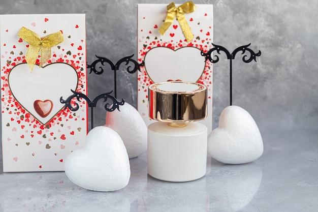 母の日、女性の日、バレンタインデーまたは誕生日。灰色の背景の香水。ハートの形のギフト、お菓子。スペースをコピーします。 Premium写真