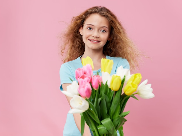 Mother's day, a young woman with a child posing in the studio with flowers, a gift for women's day and mother's day