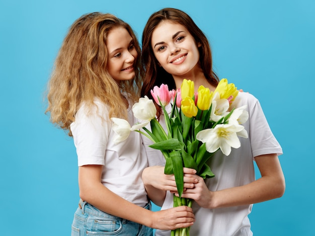 Mother's day, a young woman with a child posing with flowers, a gift for mother's day