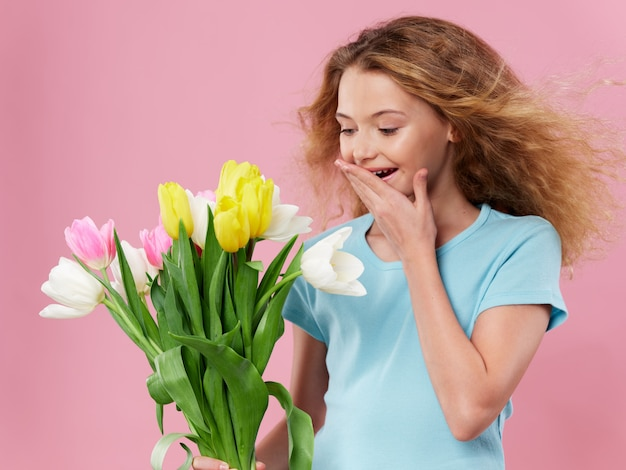 Mother's day, a young woman with a child posing  with flowers, a gift for women's day and mother's day