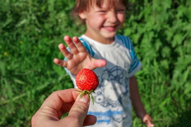 母の手が屋外の庭で幸せな子供に熟した赤い新鮮なイチゴを与えます。