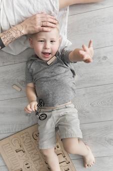 Mother's hand on little son's forehead lying on hardwood floor raising his hand